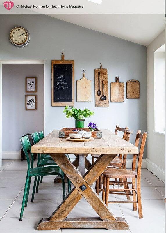 Wooden dining table with wooden chairs and green chairs.