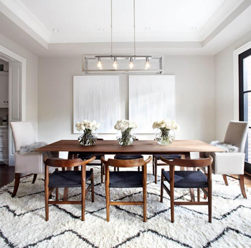 Elegant dining room with a mix of wooden and fabric chairs, a wooden table, and geometric rug.