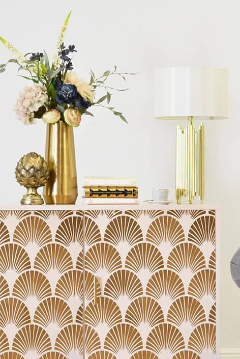 Shot of a white and gold printed sideboard with decorative accessories.