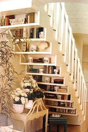 Shelves on the underside of a white staircase.