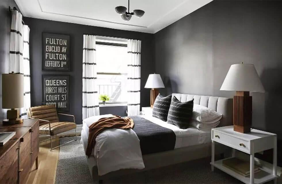 Black and white bedroom with wooden lamps, wooden chest of drawers and wood flooring