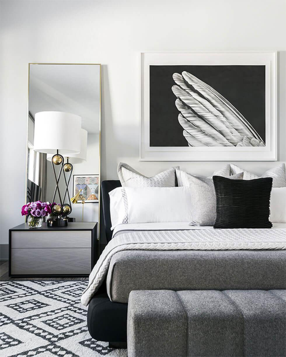 Modern black, white and grey bedroom with large bed, wall art and a mirror