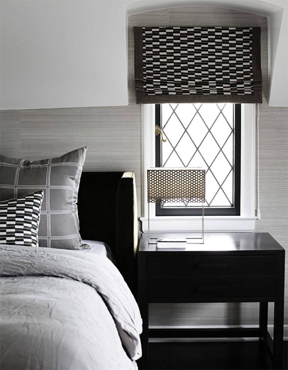 Black and white bedroom with patterned blinds and cushions