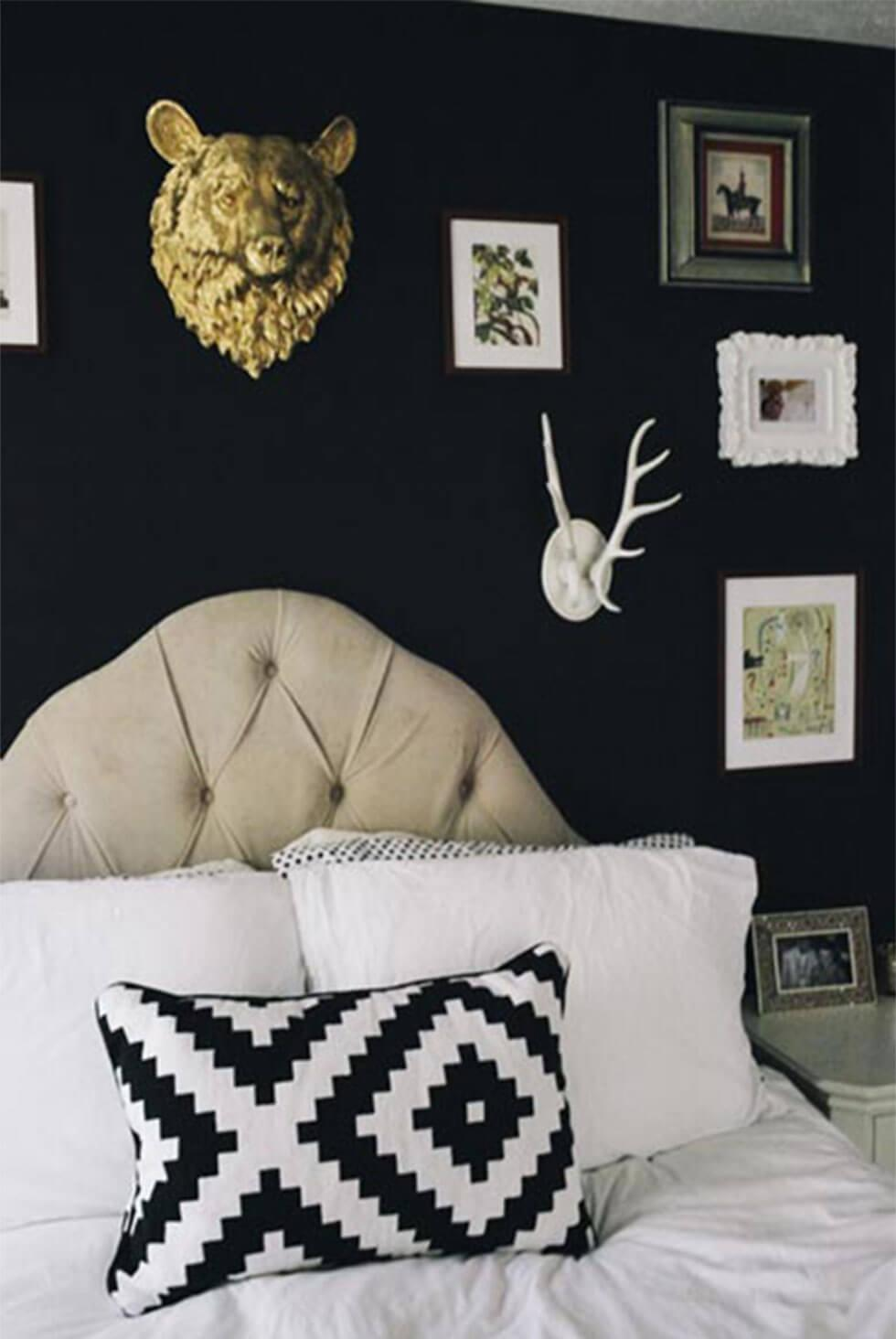 Quirky black bedroom with art and wall decor, printed cushion and upholstered headboard