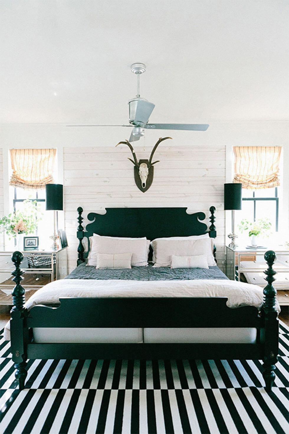 Classic black wooden bed in a white brick room with black lamps and modern, printed rug