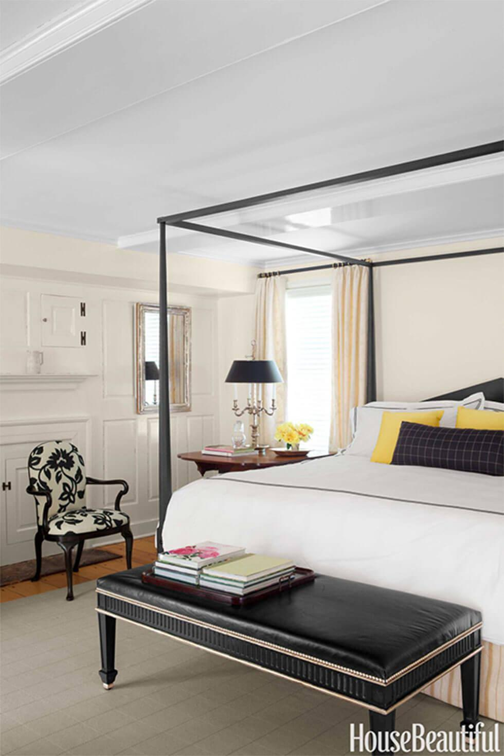 Classic black and white bedroom with floral armchair, four poster bed and bright yellow cushions