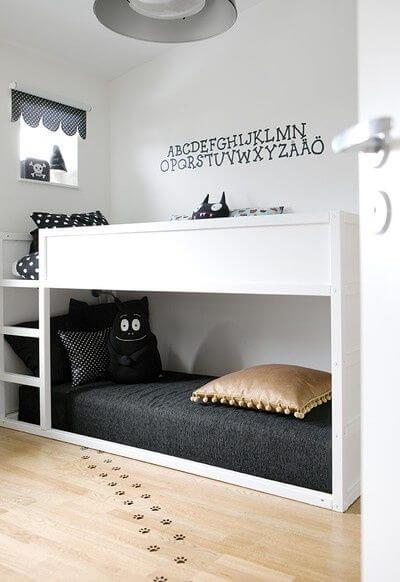 White child's bed with storage space, and black decor and decals.