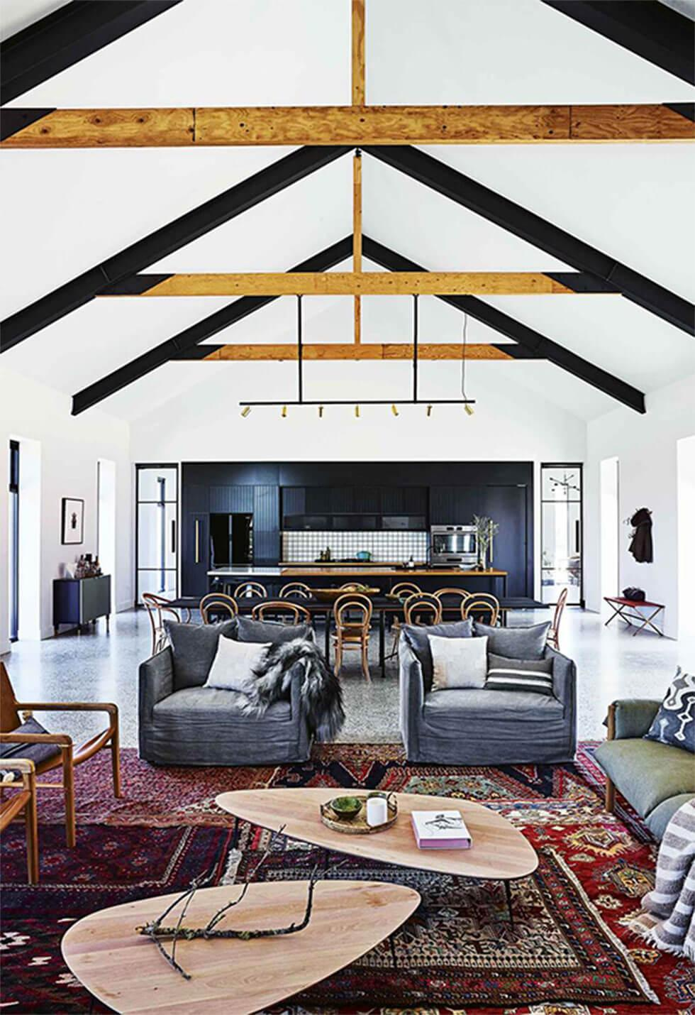 An open plan farmhouse living space with high ceilings and exposed beams, layered rugs, a dark feature wall and large grey armchairs
