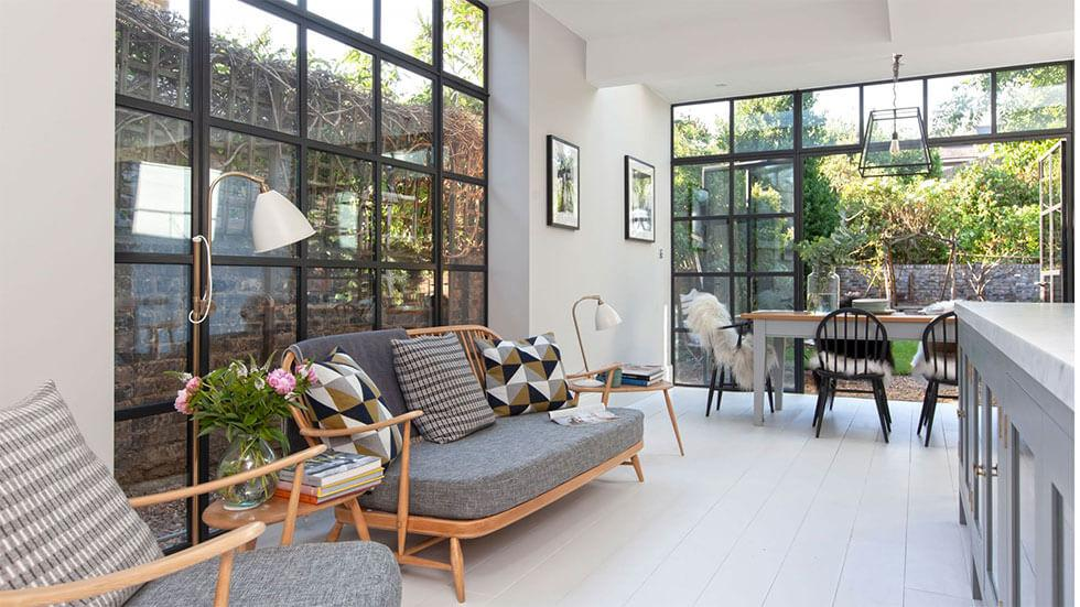 Open plan living area with large glass doors that open out into the garden, and a palette of wooden tones and grey hues.