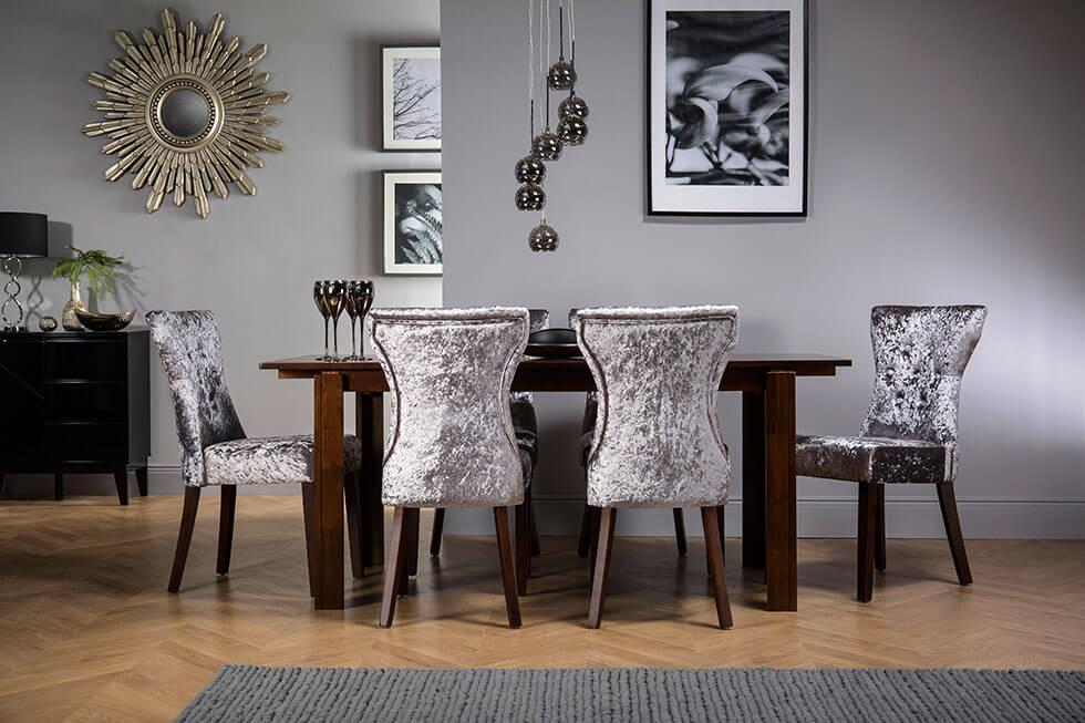 Velvet dining chairs paired with a dark wooden table.