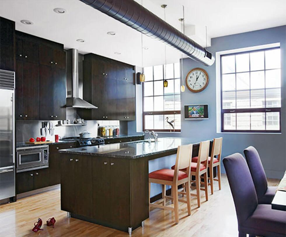 Modern dark blue open plan kitchen and dining room with modern stainless steel appliances