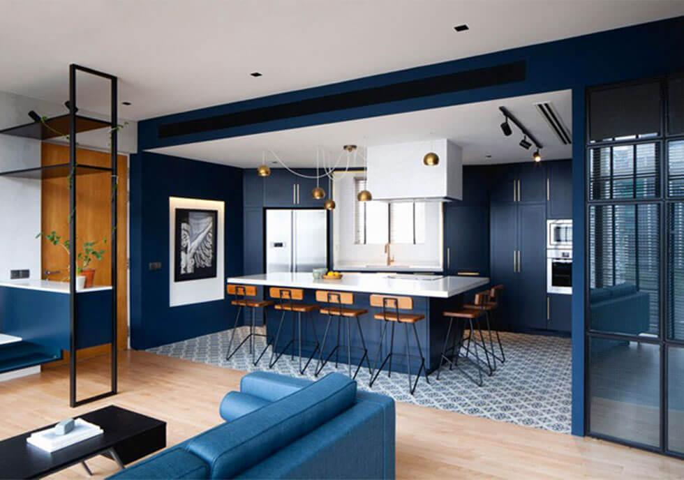 Spacious dark blue open plan dining room with colourful tiles in the kitchen and wooden flooring in the living area.