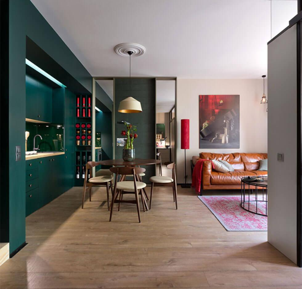 Colourful, eclectic open plan kitchen, dining and living room with a dark green feature wall, pink rug and low lamp.