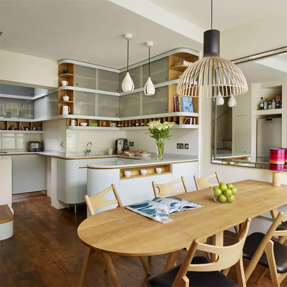Open plan kitchen with rounded curves, wooden table and chairs, and statement lamp.