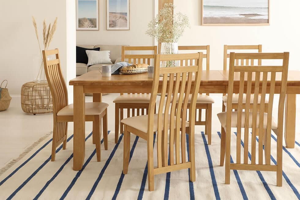 Nautical inspired dining room with oak wooden dining table and slatted back wooden dining chairs.
