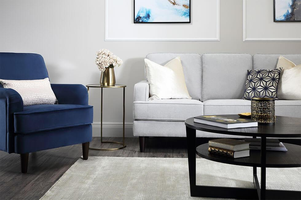 Modern living room with grey fabric sofa, dark blue armchair, white cushions and feature wall
