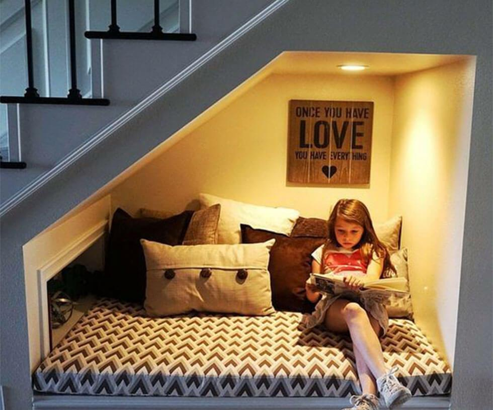 child relaxing in reading nook under the stairs