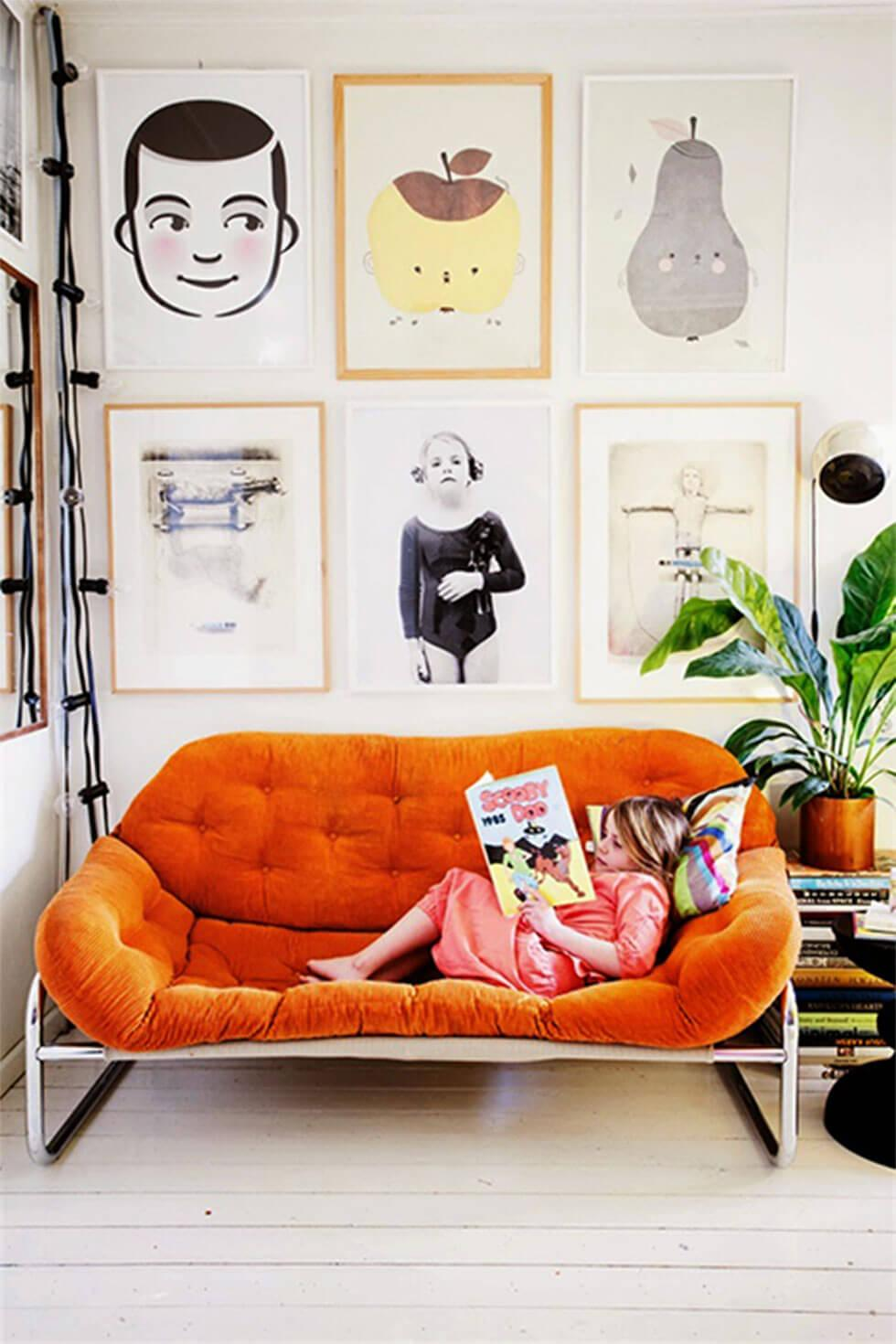 child reading in large orange armchair with big photo frames hanging above