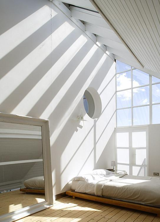 High-ceilinged bedroom with mattress on the floor