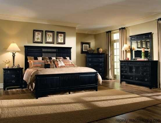 Large bedroom with a big black bed and warm lighting