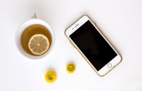 iPhone with lemon tea and yellow flowers
