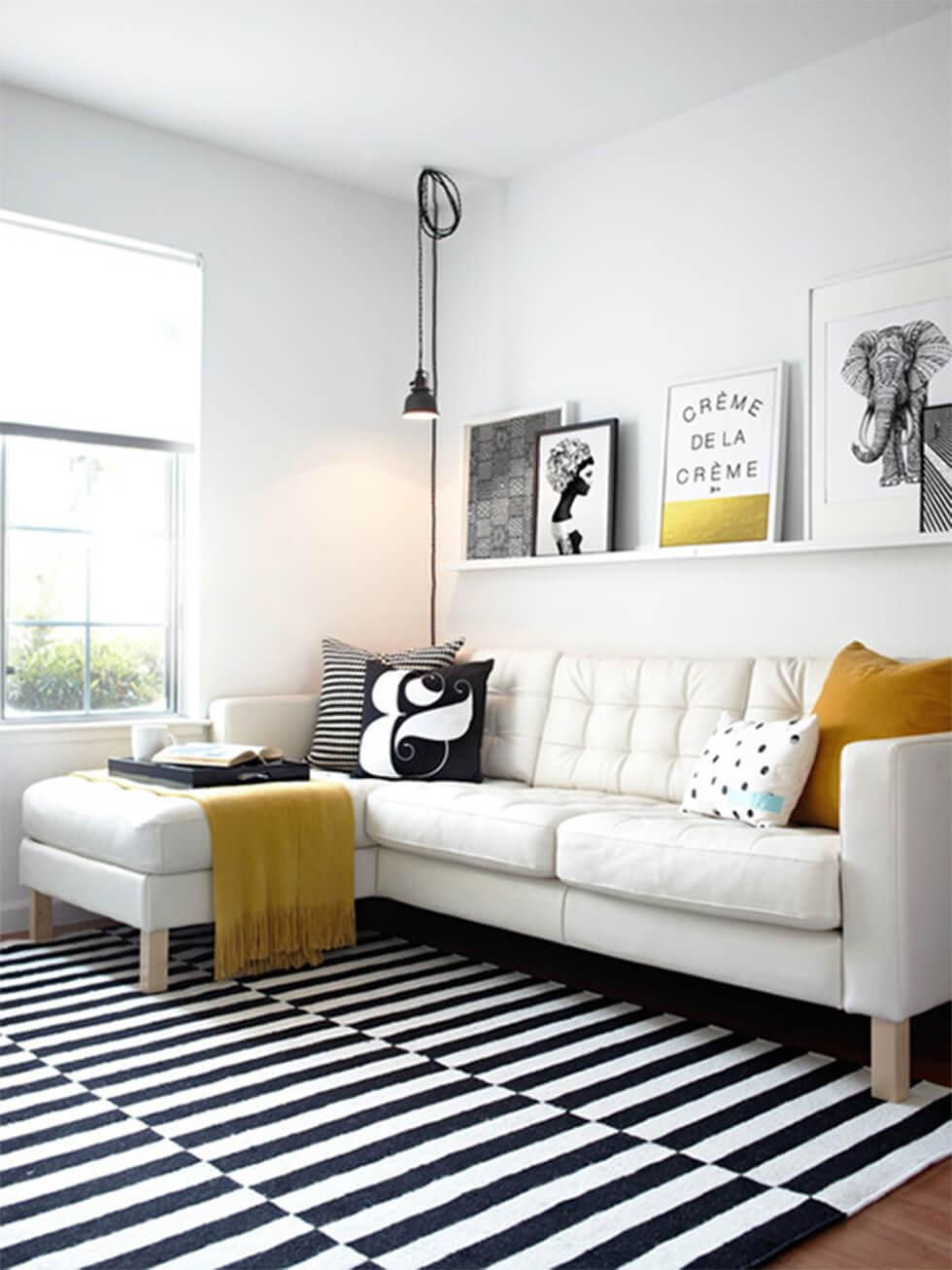 Cosy white corner sofa with a black and white rug in a bright and airy living room.