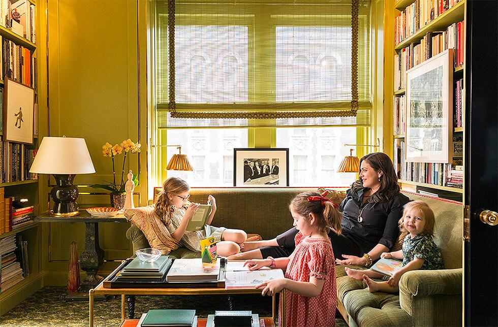 A family lounging on a classic green corner sofa