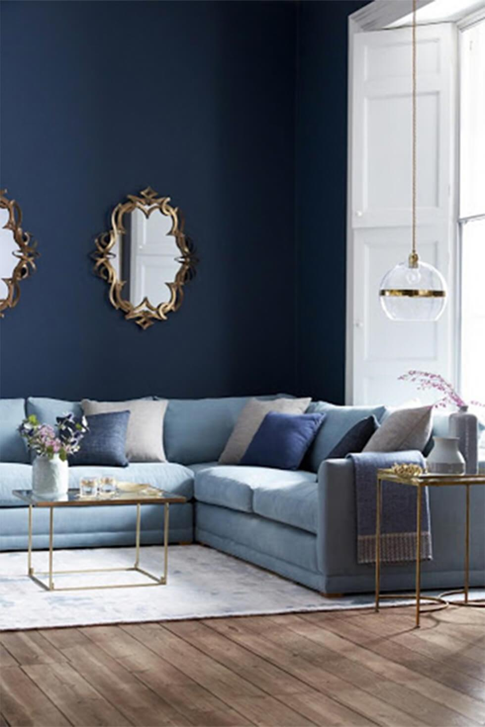 Light blue corner sofa in a cosy living room with navy walls.