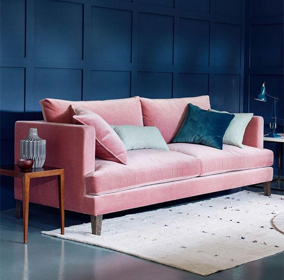 Pink velvet sofa with colourful accessories and striking classic blue walls in the background