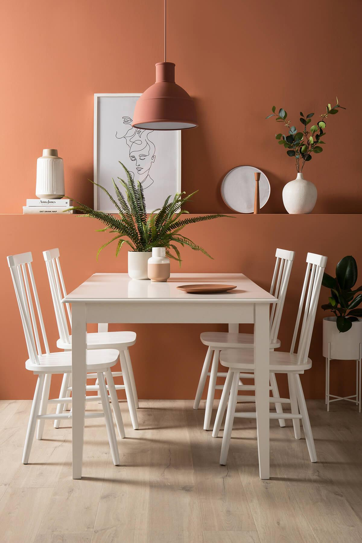 Nordic design inspired dining room with canyon clay walls and white dining set.