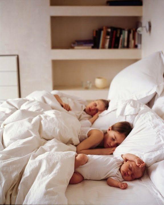 Three children asleep in a bed