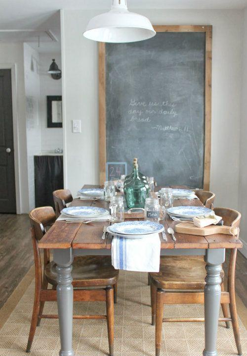 Wooden dining table with large grey legs and a chalkboard on the wall