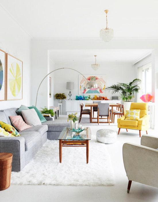White living and dining space with grey sofa, yellow armchair and bright colours.