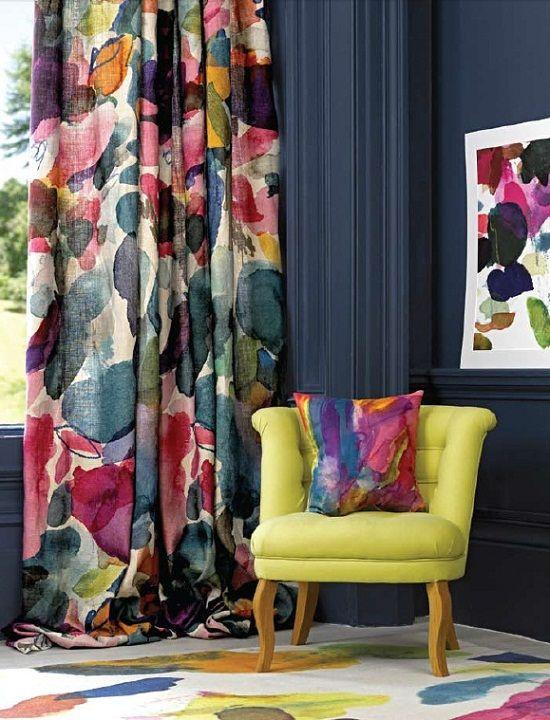 A yellow armchair set against a colourful floral curtain, with a patterned carpet and pillow.
