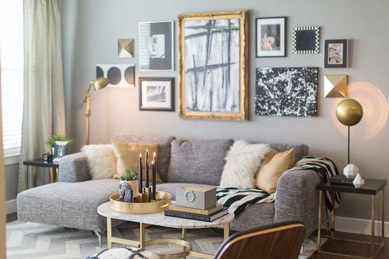 Large grey sofa, pink and white pillows, framed photos on the wall.