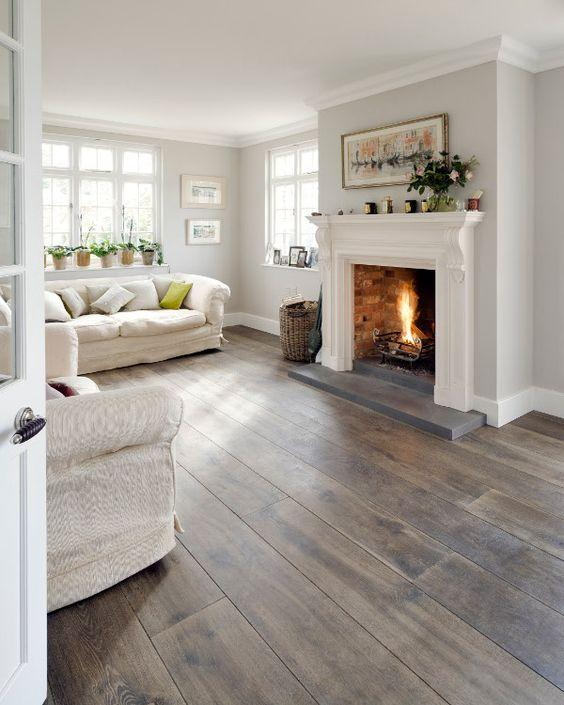 White living room with wooden floors and a fireplace.