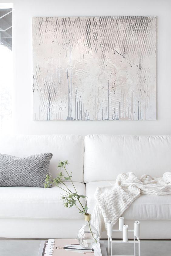 An all-white living room with a white sofa, white knit throw, white side table, and a grey pillow and artpiece.