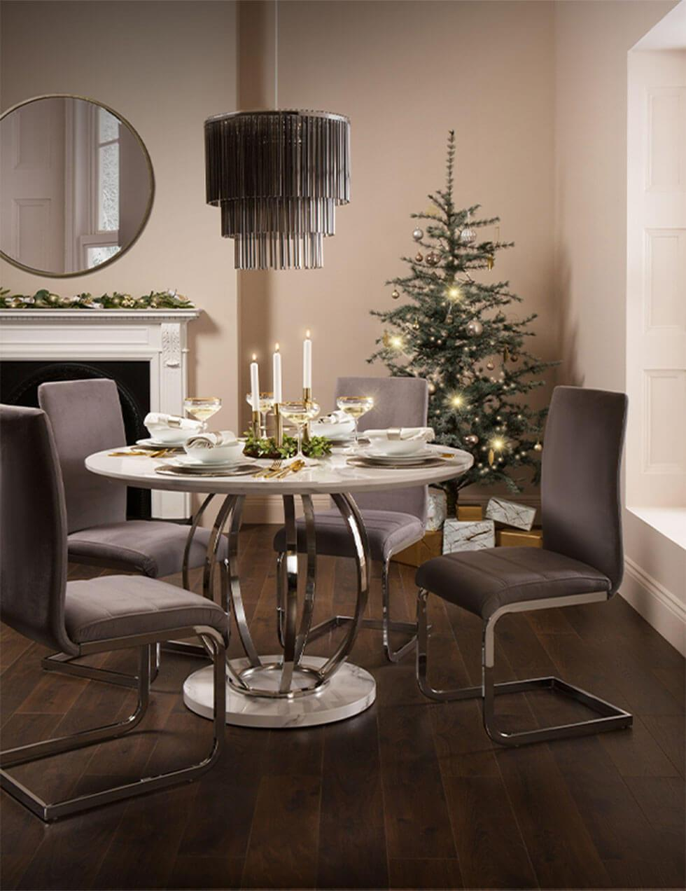 Chandelier above a white marble dining table in a glamorous Christmas setting.