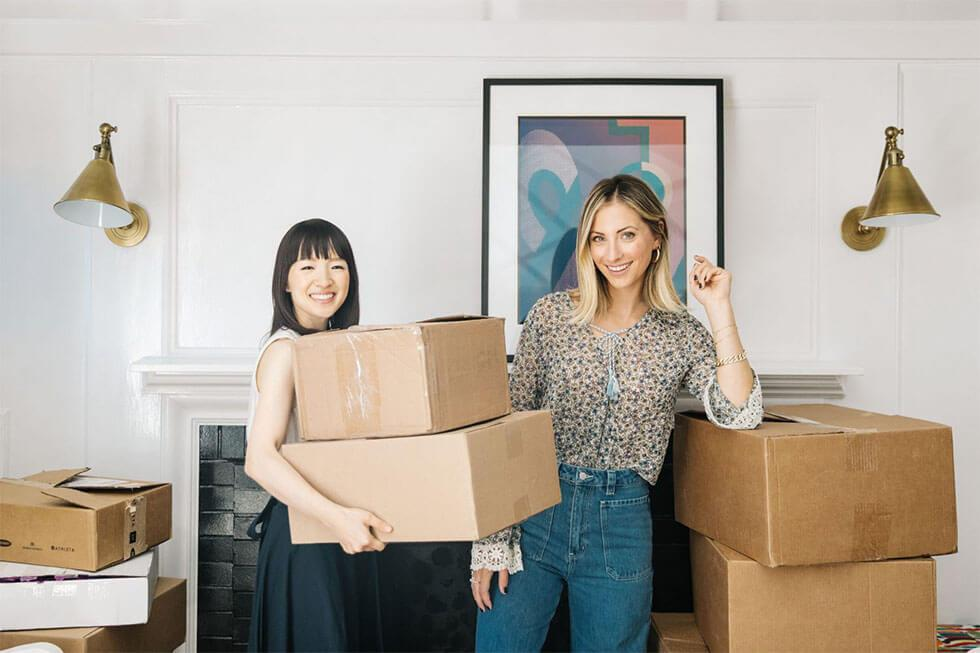 Marie Kondo and Emily Schuman holding a pile of boxes