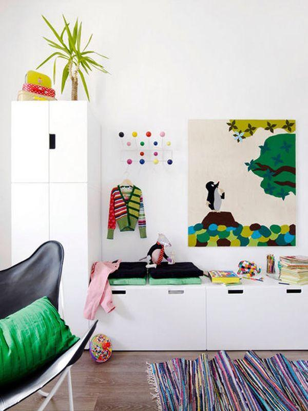 Colourful child's room with white cabinet and bright art and printed rug.