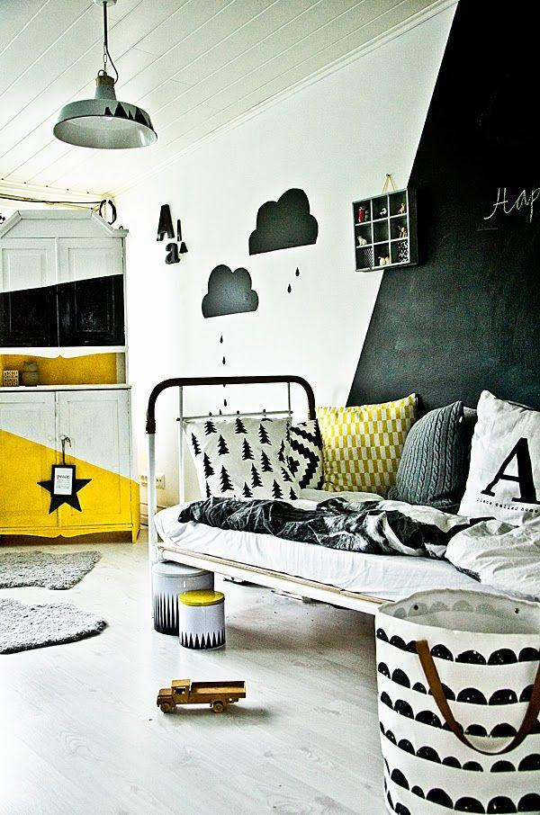 Bedroom with graphic black and white rain cloud decals, and other monochrome prints, with pops of yellow