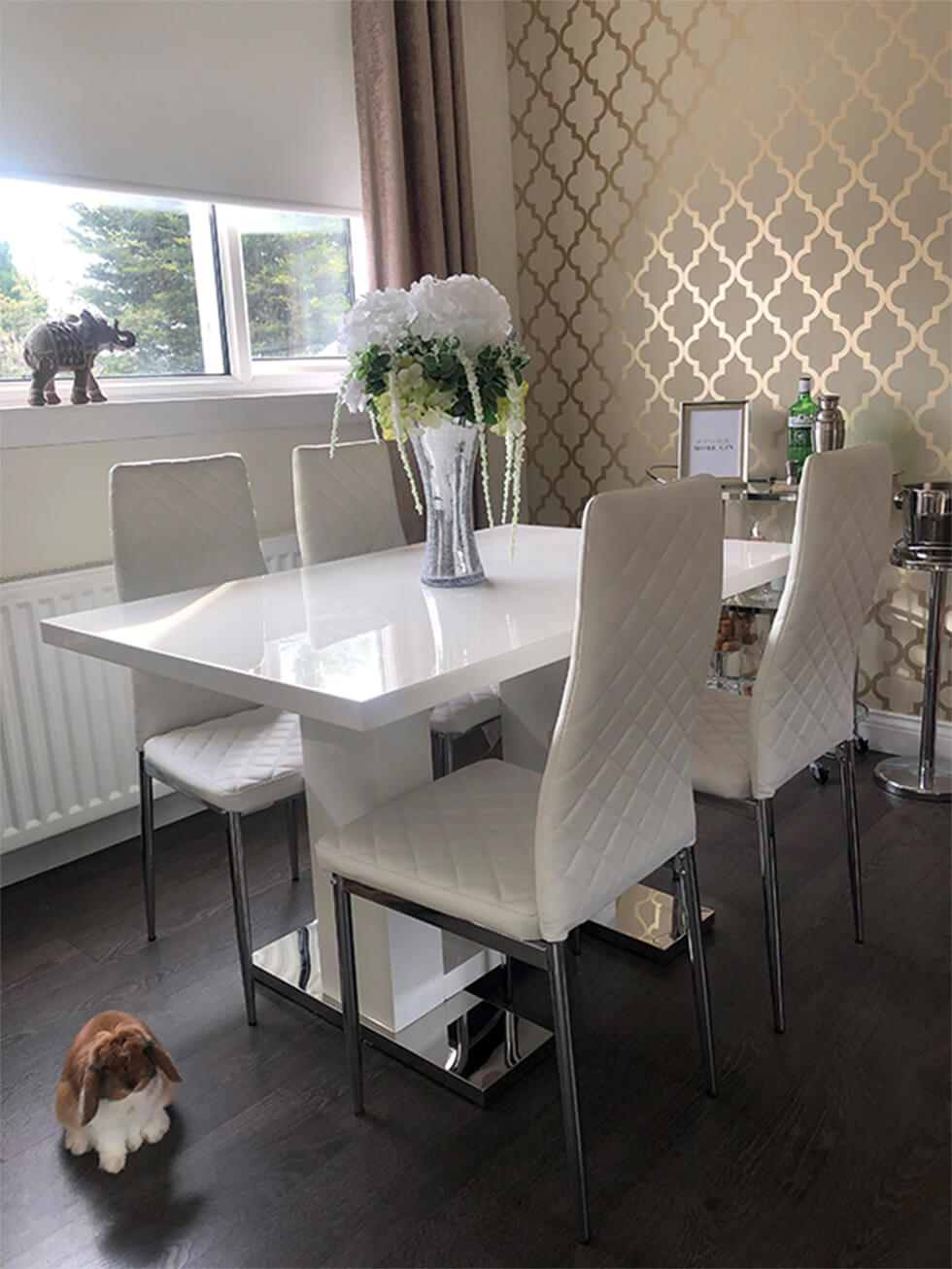 White high gloss dining table with white leather dining chairs in a modern dining room