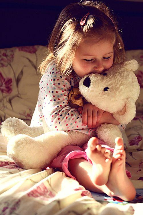 Young girl hugging a white teddy bear.