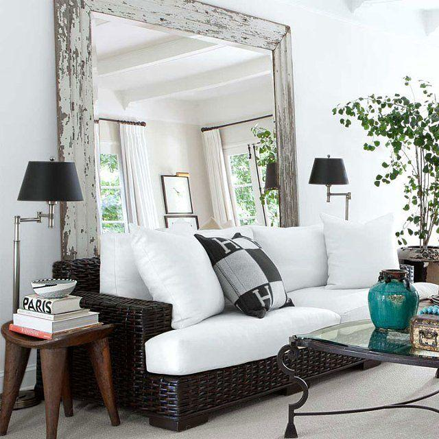 Monochome sofa in front of a large mirror.