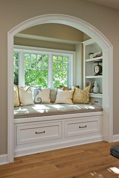 Window seat with pillows and bottom drawers.