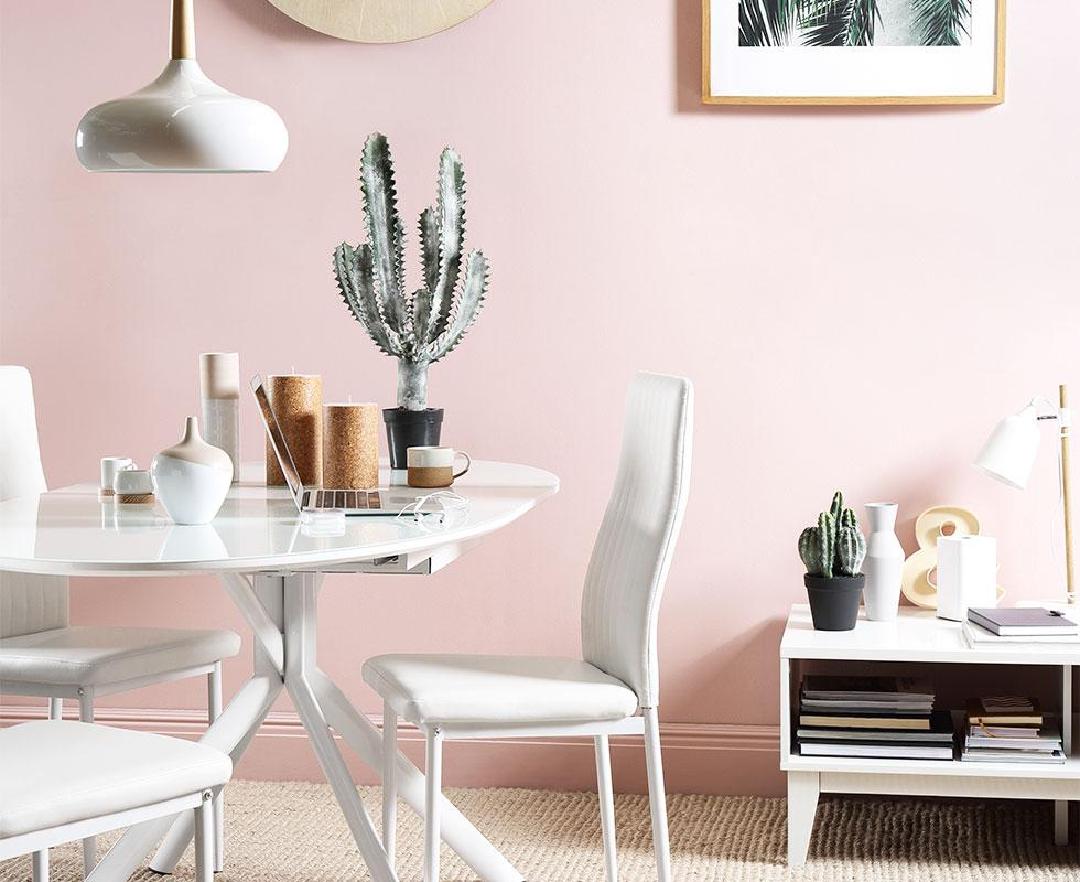 White dining set in a pink room.