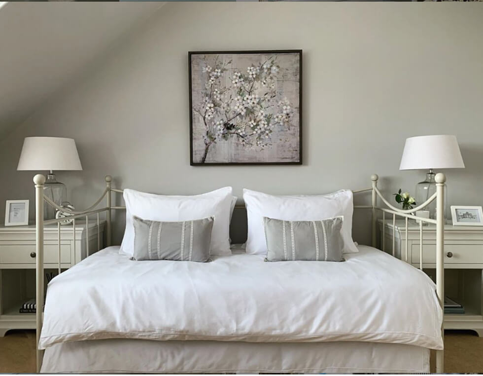 Cosy neutral bedroom with white bedding and grey walls