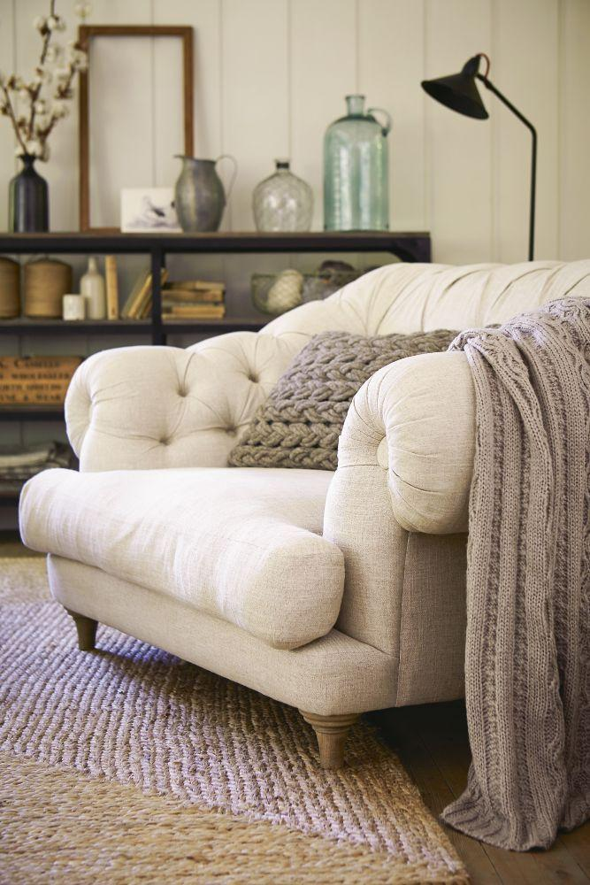 White sofa with knitted pillow and throw.