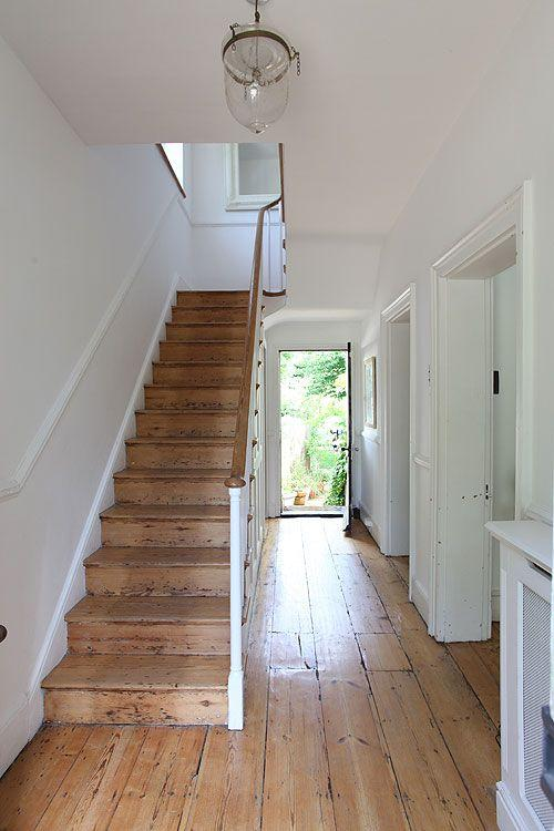 White hallway with wooden stairs.
