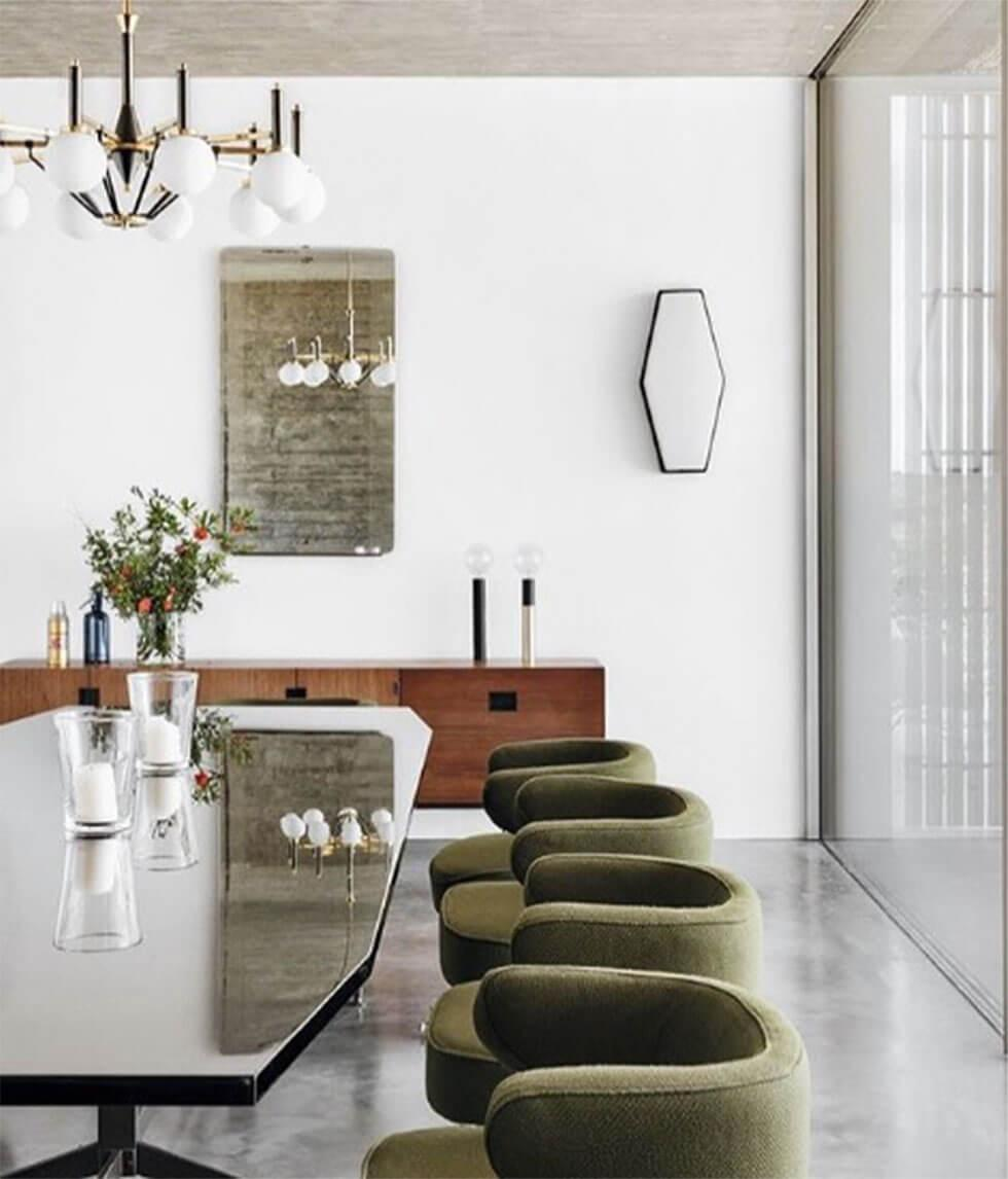 Curved green chairs with uneven shaped table in white dining room with statement lighting
